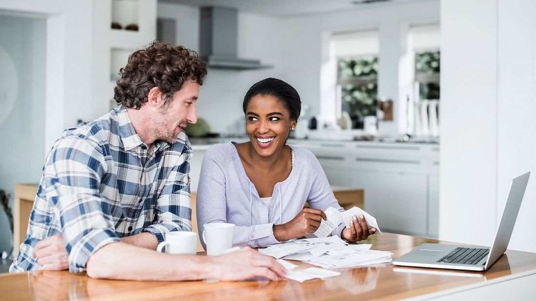 Couple at a table discussing the financial steps to take before applying for a mortgage
