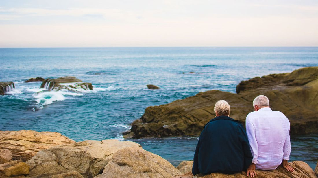 Retired couple living off the grid looking out at the ocean