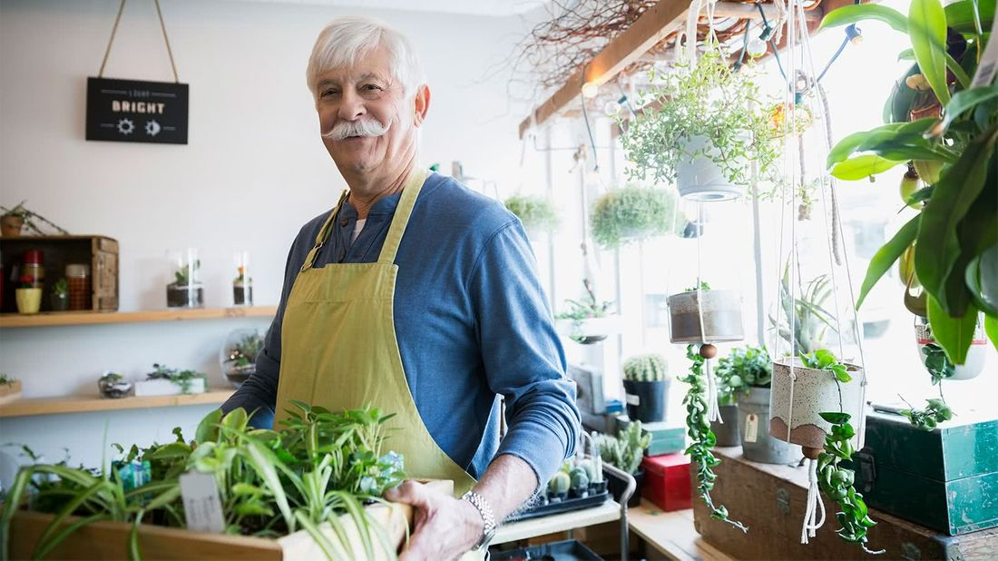 Man holding plants wondering when is the right time to retire