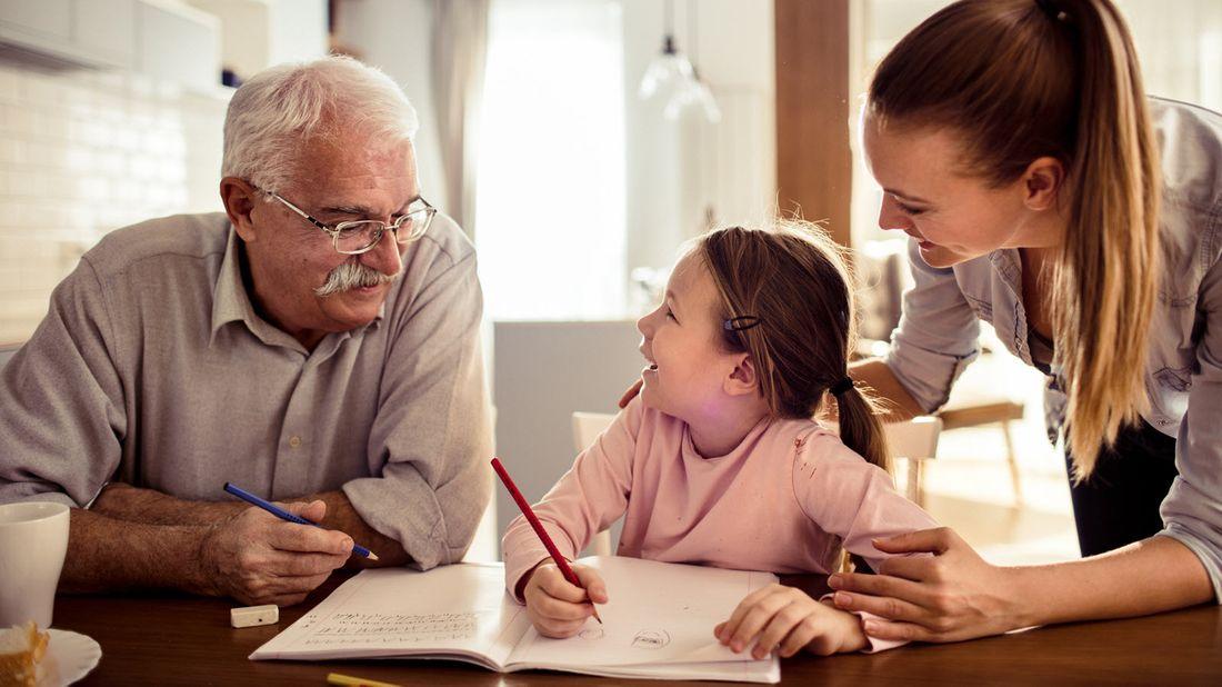 An elderly parent helps graddaughter with her homework