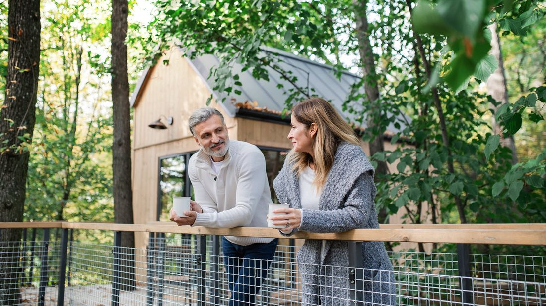Couple standing on a bridge and drinking coffee as they discuss donating life insurance to charity.
