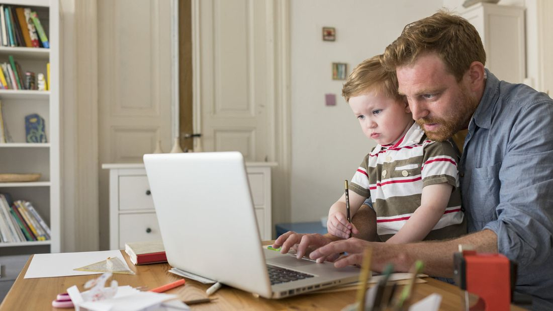 A man working from home with his son in his lap