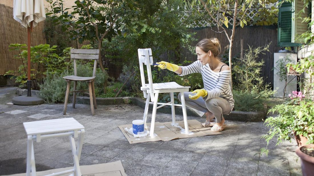 Woman painting a chair in a garden