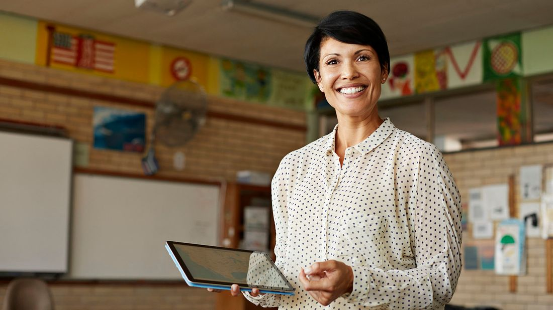teacher in classroom holding tablet