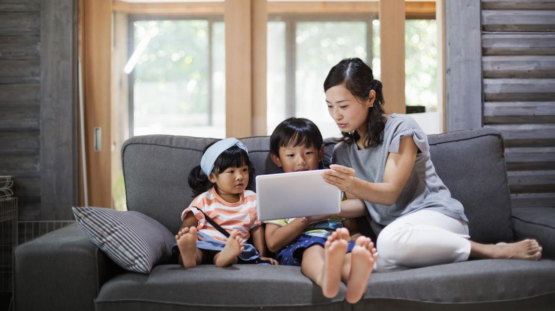 Mom on couch managing kids screen time