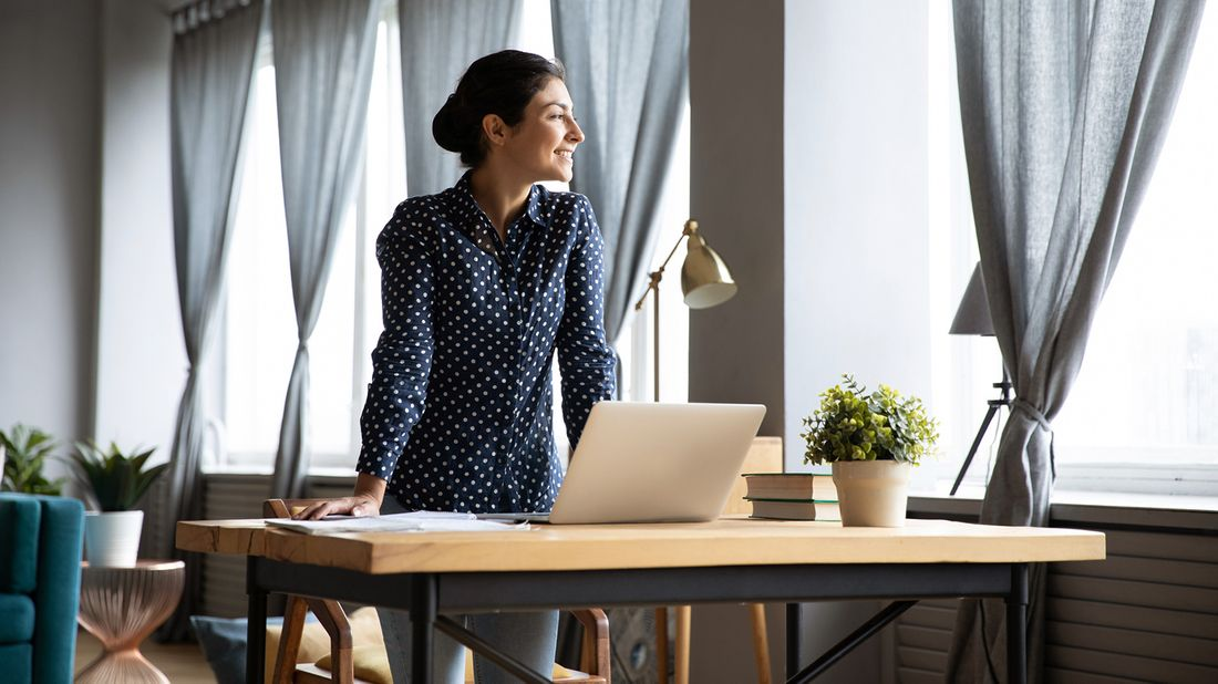 woman smiling while looking out window and standing at desk