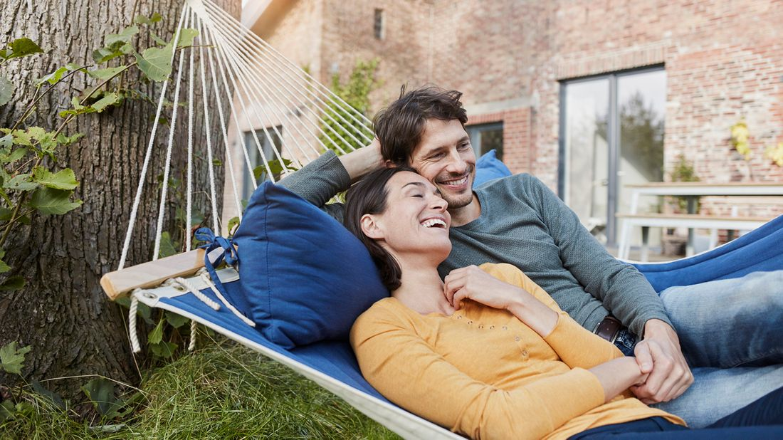 happy couple lying in hammock