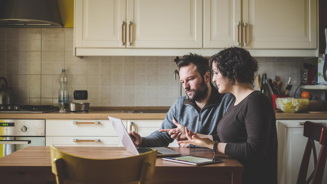 Couple trying to avoid refinancing mistakes together while looking at laptop.