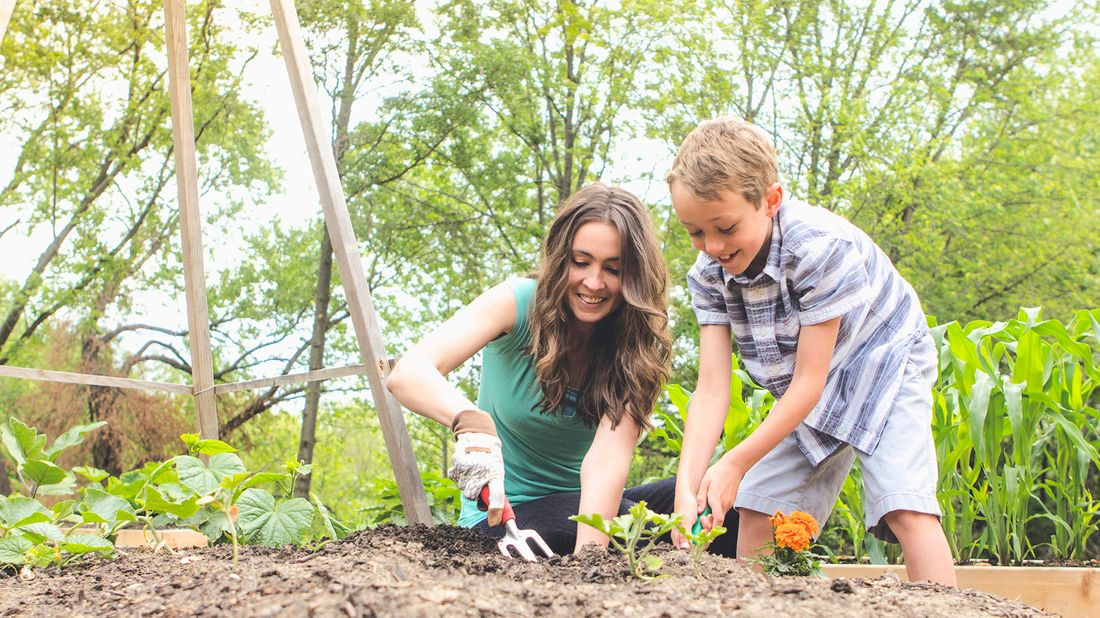 mother and son planting a garden