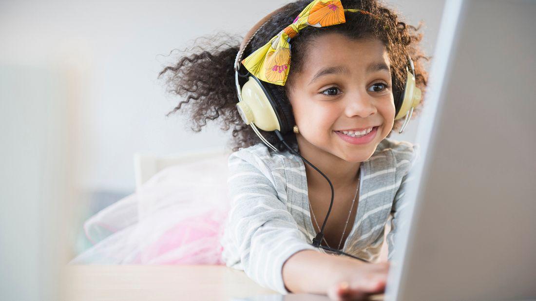 smiling girl wearing headphones while using laptop