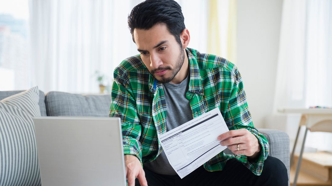 man paying bills on laptop
