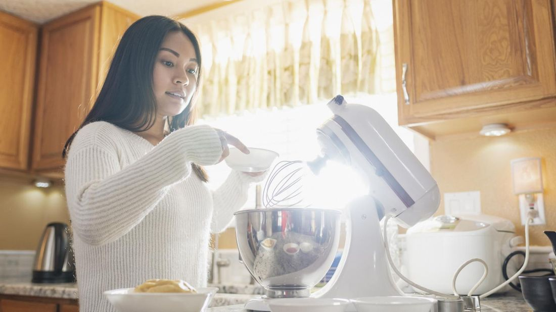woman using stand mixer to make holiday treats