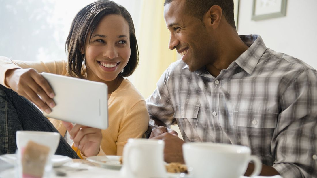 Couple looking at a tablet and discussing how variable universal life insurance works.