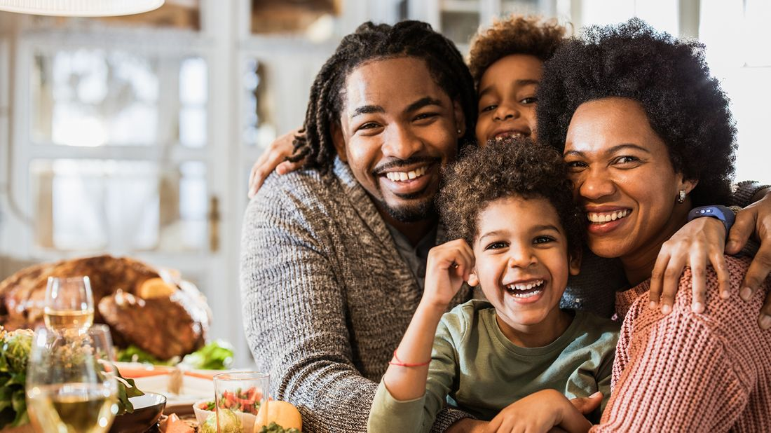 smiling family enjoying Thanksgiving dinner