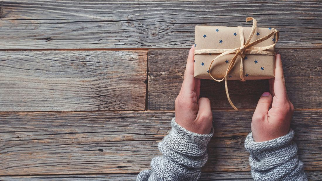 hands holding homemade gift box on wooden table