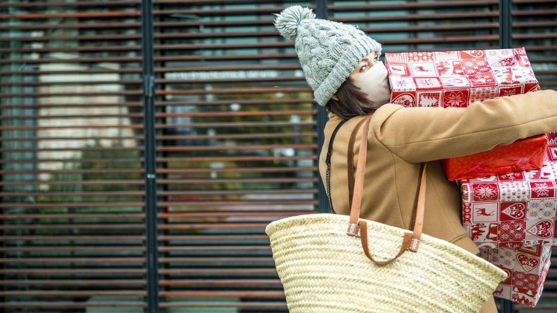Woman in protective face mask with Christmas presents