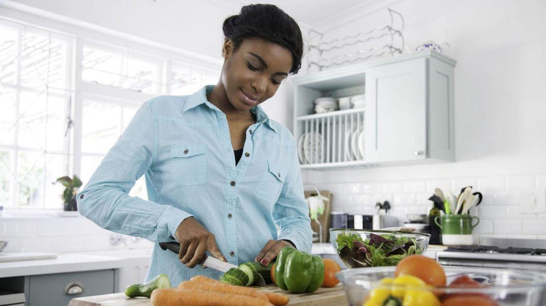 woman chopping veggies during quarantine for savings