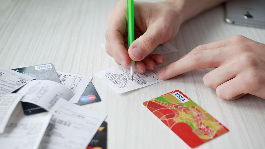 Person organizing reciepts paying down their credit card debt
