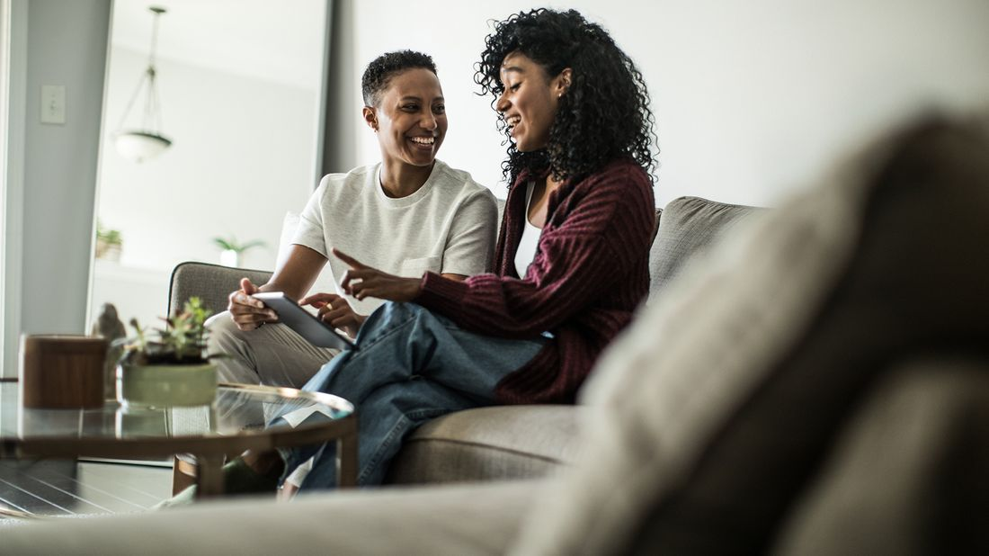 couple sitting on couch at home talking