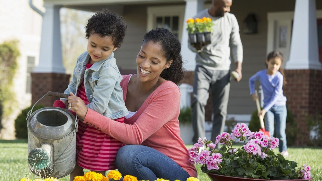 family with supplemental homeowners insurance watering flowers