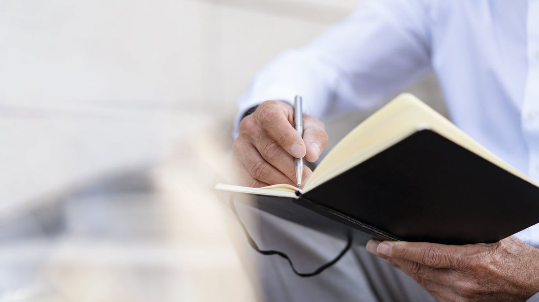 Man writing in a journal as he goes through an end of life checklist.