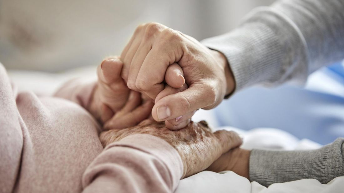 Caregiver holding hands with nursing home patient