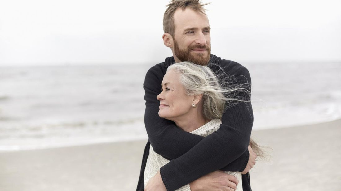 Adult son on beach hugging mother he may want to insure without telling her