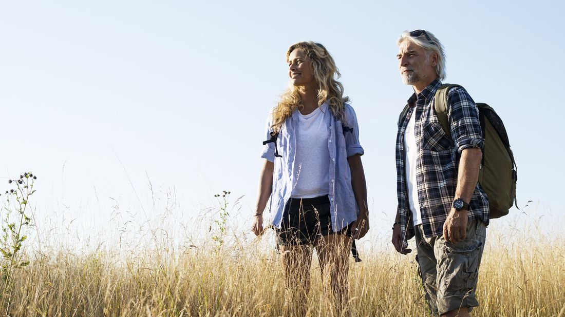 Couple hiking in a field wondering what happens to term life insurance if you don't die