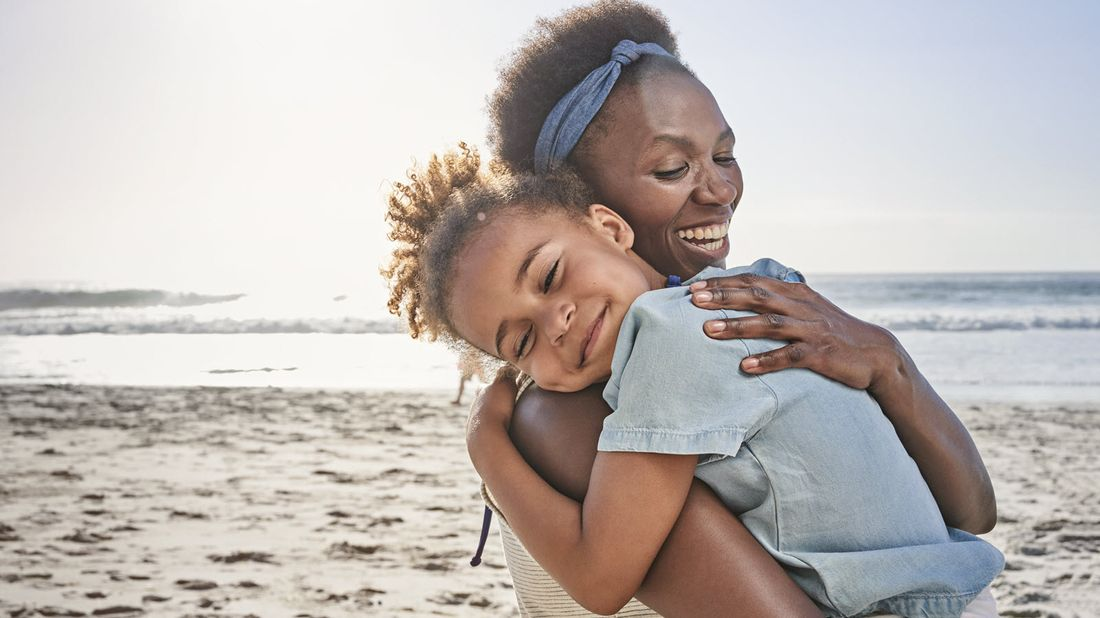 Mother with her daughter at the beach wondering how much is life and disability insurance.