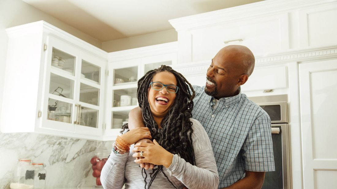 Couple in the kitchen talking about how much money they need to retire at age 50.