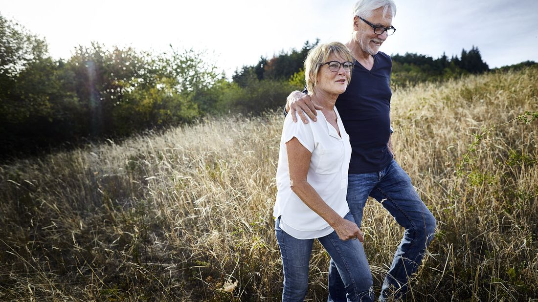 Couple walking in a field discussing when can I take money out of my 401(k)