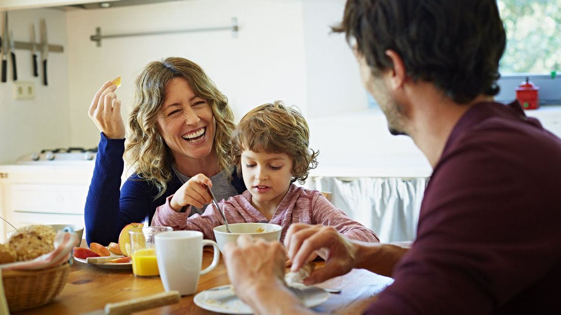 Mom and dad at the breakfast table discussing a financial planning checklist for a growing family