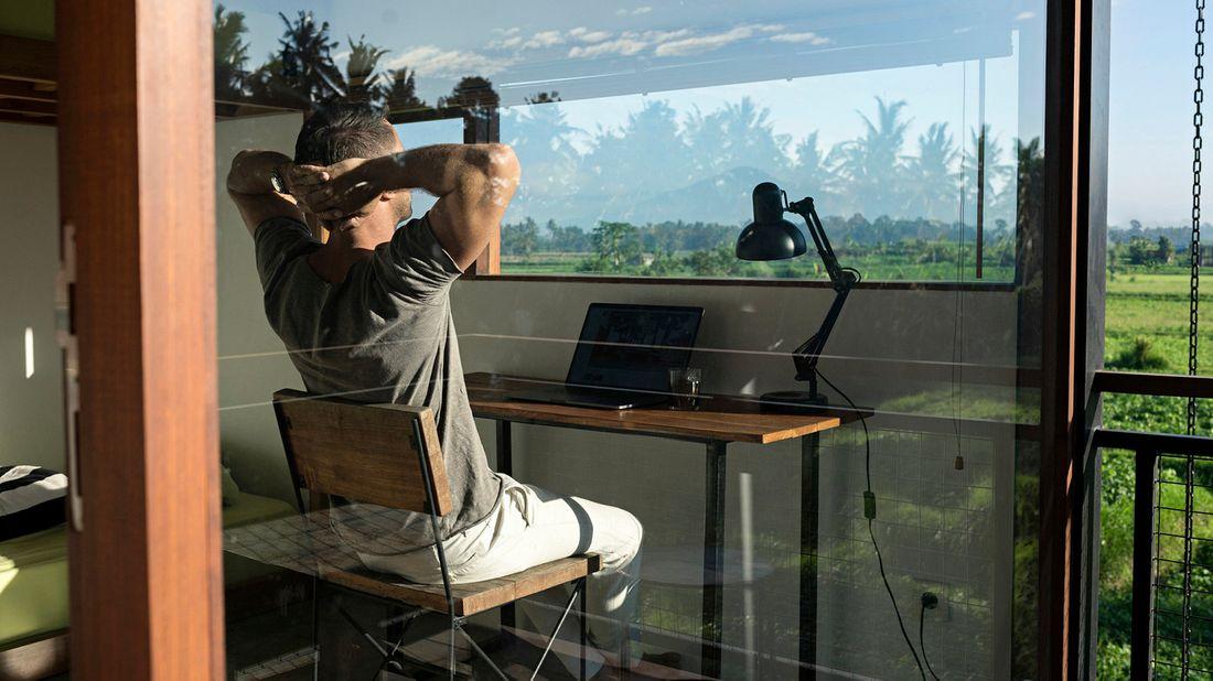 man sitting at desk looking at view