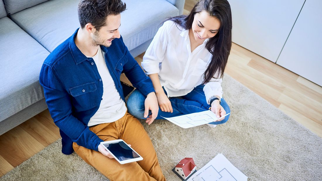 Couple with floor plans going on virtual home tour