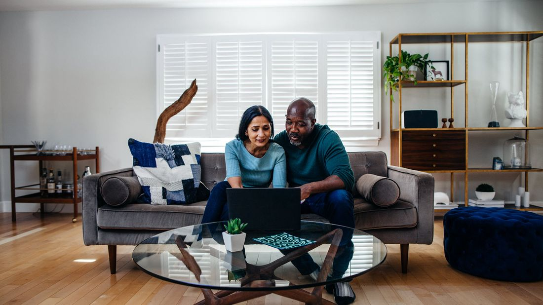 Couple on a couch researching how much money you need for wealth management services.