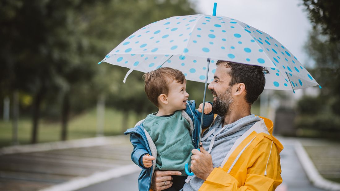 father and son holding umbrella