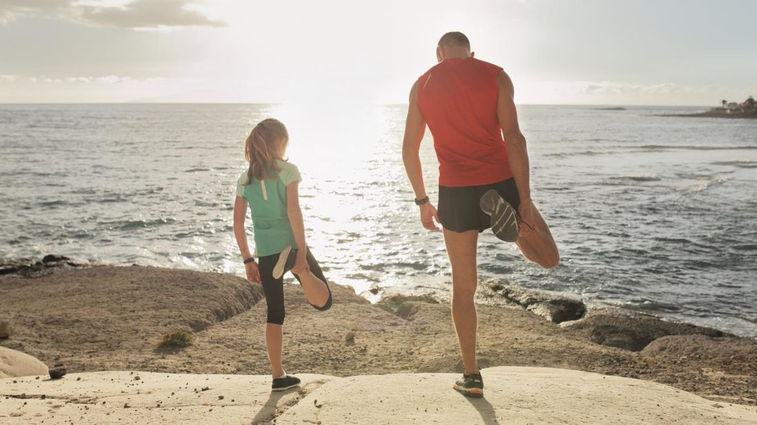 father-and-daughter-stretching-on-shore