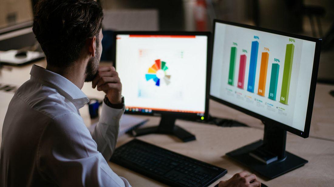man studies markets on computer