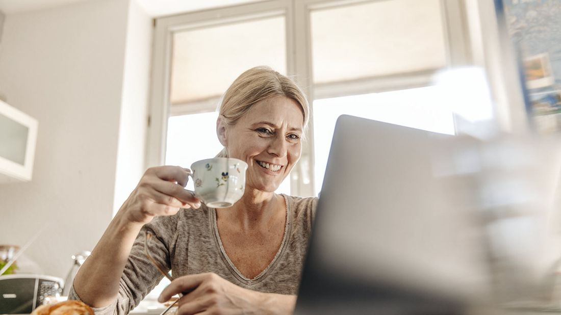 Woman drinking coffee and reading Northwestern Mutual Market Commentary