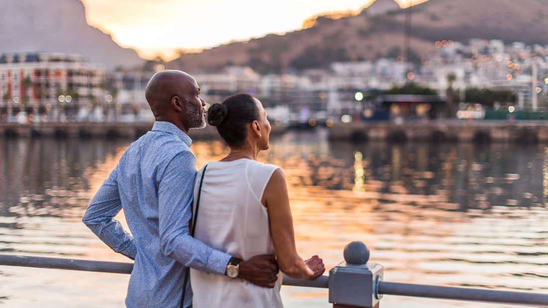 Couple standing along a river.