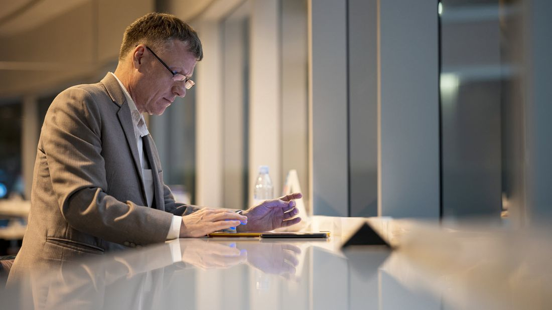 man sitting at a table and reviewing investments portfolio on a mobile device