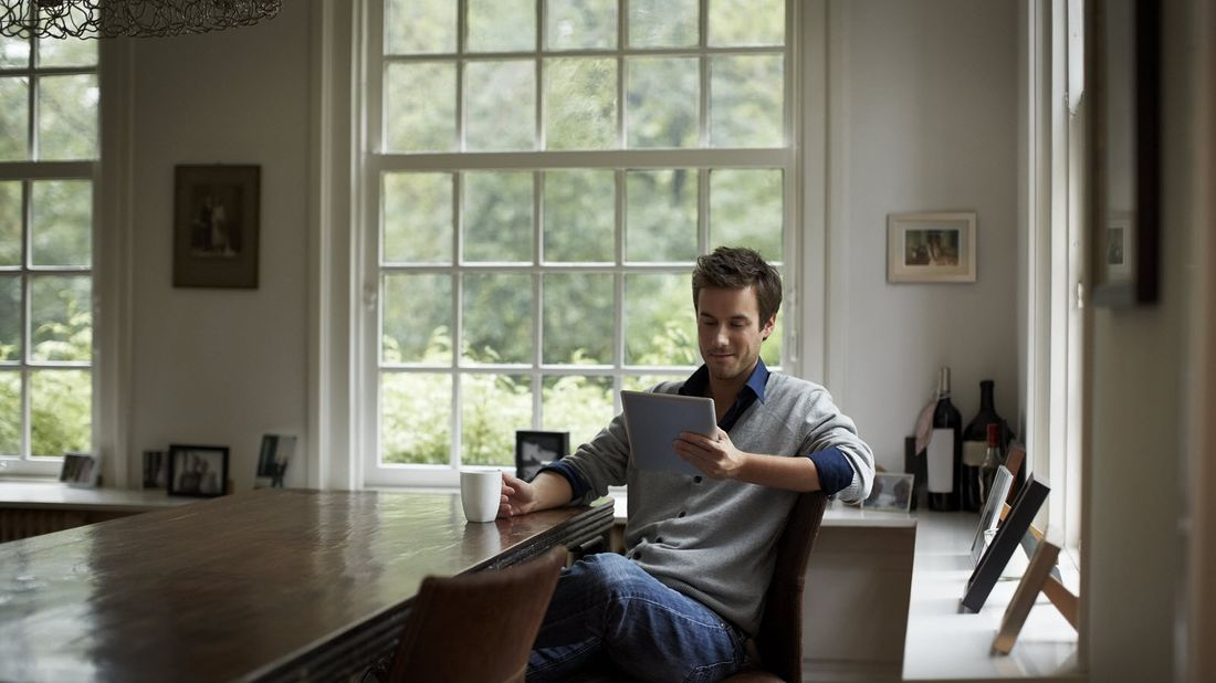 Man sitting at a table and reading Northwestern Mutual Market Commentary