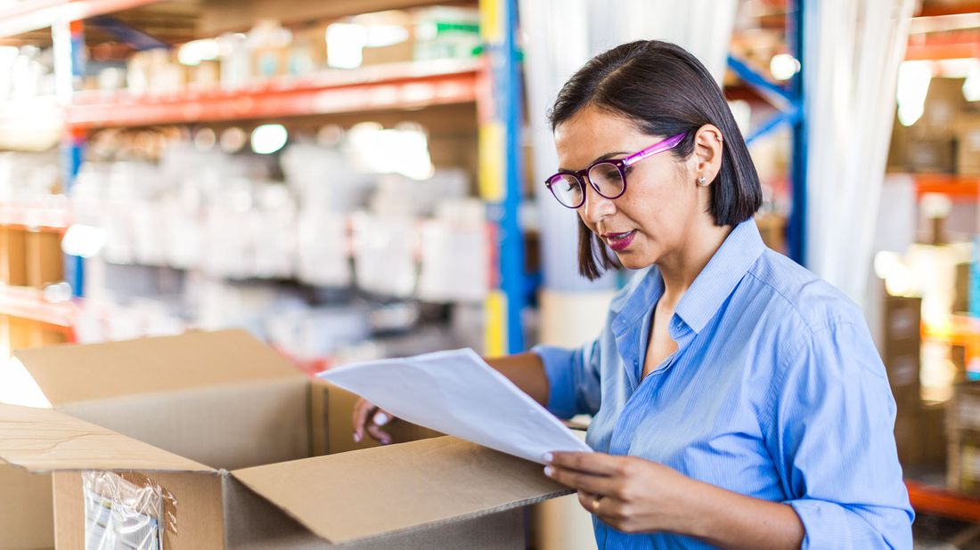 Business owner looking at shipment after reading Northwestern Mutual Market Commentary