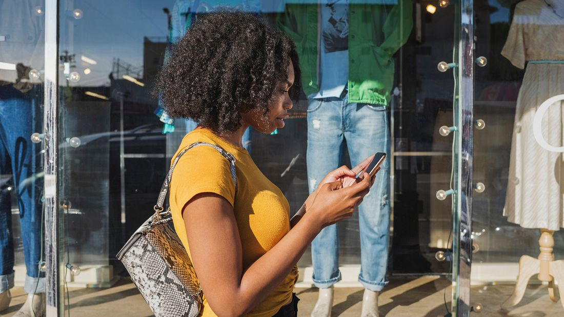 woman looking at phone while window shopping