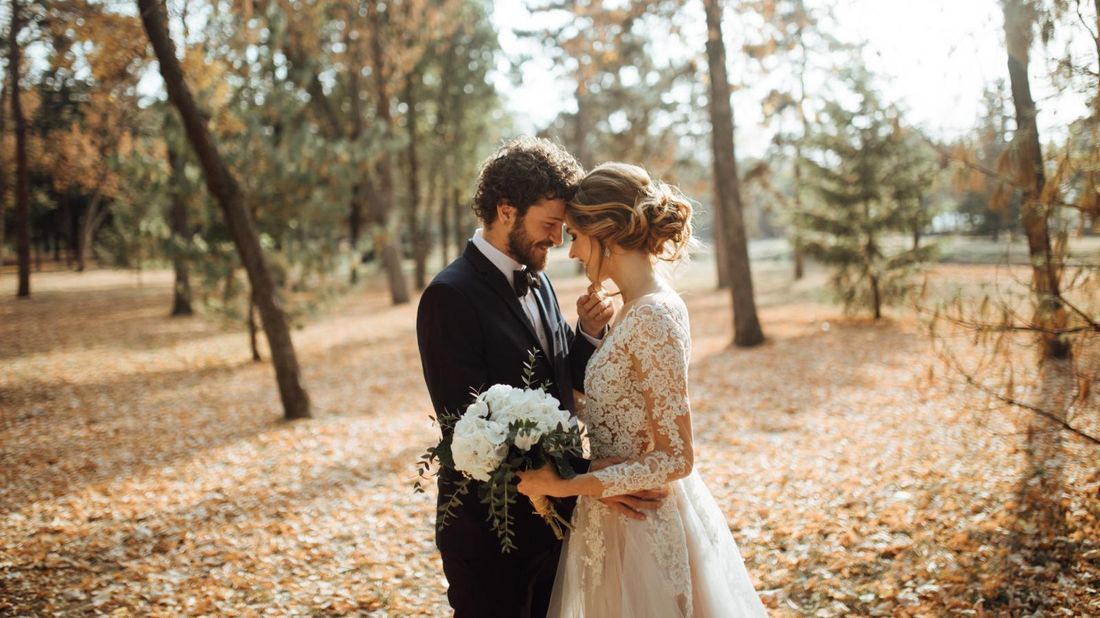 bride and groom getting married in a forest in fall who have negotiated with wedding vendors