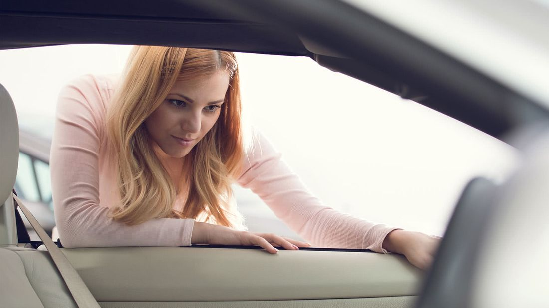 Woman inspecting a vehicle wondering how much a car really costs