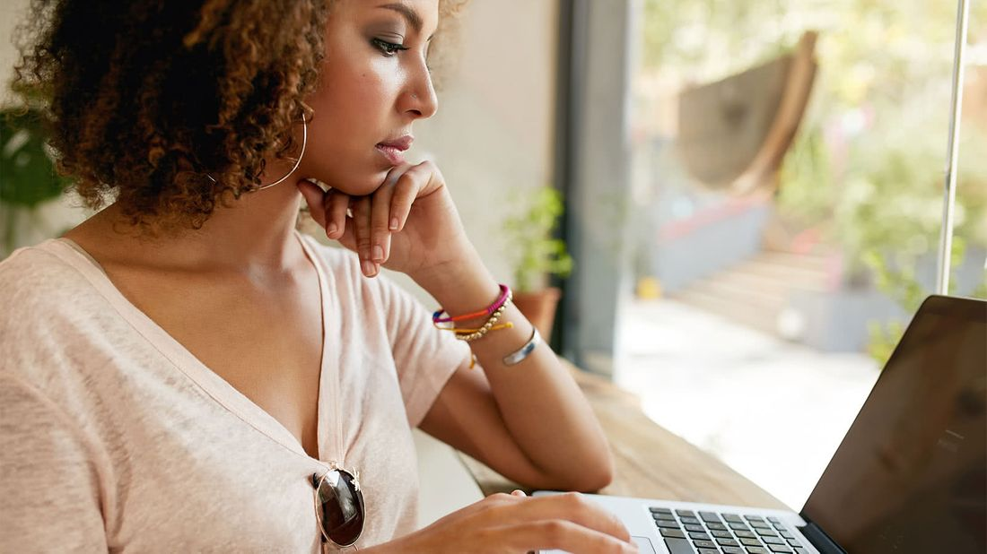 Woman working on laptop researching money rules to boost her finances