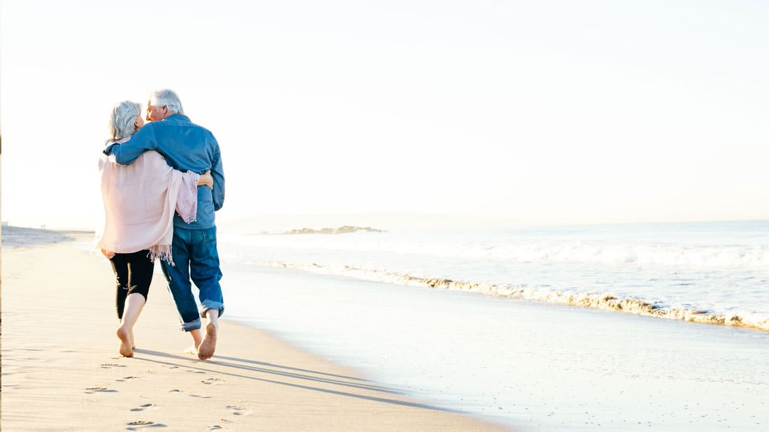 Senior couple on a beach after discussing retirement with a financial advisor