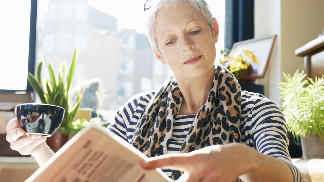 Woman reading about ways the coronavirus is impacting finances for retirees.