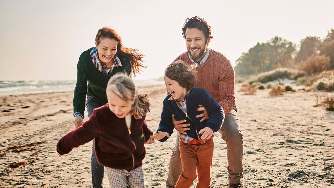 Family on beach after keeping their financial resolutions